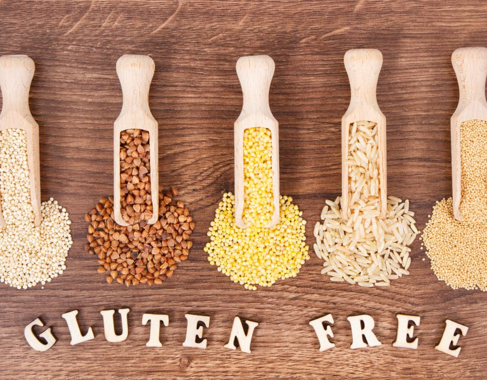 Inscription gluten free with groats, brown rice, amaranth and quinoa seeds on rustic board, concept of healthy food and nutrition